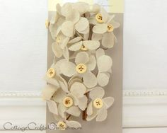 """Charming 1 3/4"""" linen flower picks with a wood button center. Each of the 16 flowers is attached a wire stem, 4 1/2"""" long. Part of the David Tutera line for Darice Craft. So many uses for your rustic party or wedding decor: Tuck them into florals, embellish your cake, use on candle holders, to mark place cards of special guests.   Available from the Cottage Crafts Online shop on Etsy, where we help your ideas become creations."""