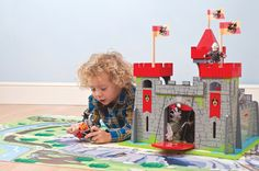 Little boys will have hours of fun with this imposing 3 tower painted wooden castle  from Le Toy Van, featuring grey stone walls with red trim and complete with 3 black dragon motif flags.