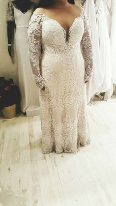This jaw dropping plus size lace mermaid wedding dress from Studio Levana on fittings. It has an off-shoulder look, deep V neck long sleeves and a stunning crocheted laces