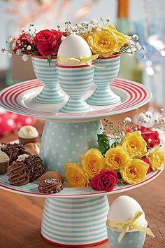 O prato de andares acomoda delicados arranjos de flores e os bombons decorados. No andar de cima, os potinhos dão suporte às rosas e ao ovo, que recebeu uma fitinha de cetim