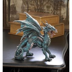 Add some fierce style to your bookshelf or desk with this fantastical dragon statue. This finely detailed beast stands on all four with wings spread, and is captured mid-roar.