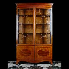 11924: A good quality mahogany and kingwood banded and inlaid bowfronted bookcase /collectors cabinet in George III style, with a seperate moulded cornice, a pair of finely astragaled glazed cabinet doors wi