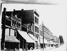 Looking north on Pearl Street between Third and Fifth Avenues the west side buildings can be seen. Starting on the left is the Owl Drug Store, the Kleinberg Building, Boss Bakery, the Geddis Building, the Cadwell-Olympic Building and the Horton Hotel. Many of the two story buildings offered hotel and lodging accommodations on the second floors.  Date	ca. 1900.