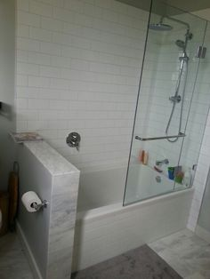 Shower tub combo w glass wall.