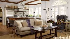 "Designers Barbara Westbrook and Kim Winkler opened the kitchen of an Atlanta house to the family room. ""The space had to accommodate a family of five, as well as a lovable golden retriever, Westbrook says. ""The openness makes it easy for everyone to mingle and not feel separated. But it was important that the two rooms look coordinated."" Those chose a neutral and white palette, with a mix of rustic antiques and unfussy contemporary pieces. Stainless steel Sub-Zero."