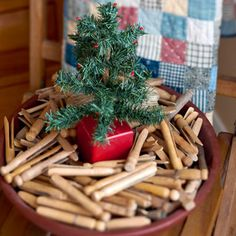 Christmas Clothespin Pot  Find a decorative use for all those old clothespins by adding them to a wide bowl with a tiny Tannenbaum. Cut a hole in a decorative jewelry gift box and stick in a real or faux evergreen sprig fashioned as a Christmas tree. Nestle the box in the clothespins for a cute potted plant. Small pops of red glitter glue on the ends of tree branches give a touch of color.