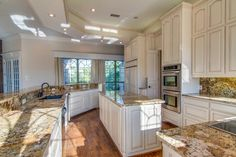 White kitchen with granite countertops and backlash, island, stainless appliances and a walk in pantry