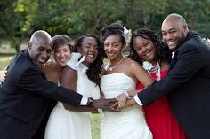 Lesbian couple Aisha Mills and Danielle Moodie, with their family, pose at their wedding for Essence magazine
