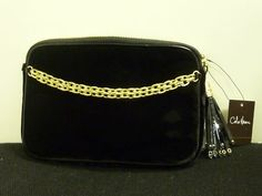 Cole Haan Black Velvet Clutch Genuine Discounted NWT . $100.00. PERFECT GIFT!!Genuine Cole Haan Black Velvet Clutchwith Gold Chain Tassel AccentsClutch has Gold Zipper Pocket Across Topwith Inside Credit Card PocketsNew, Never Used with Original TagsManufacture Suggested Retail Price is $195WONDERFUL COLE HAAN HANDBAG NEW WITH TAGS!!! .