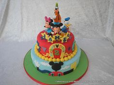 Disney Cake. Disney themed two tier birthday cake decorated in brightly coloured icing with bright yellow accents. Topped with models from Disney (Mickey Mouse Minnie Mouse Donald Duck Goofy) and sugar stars spelling the childs name