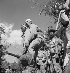 A Gurkha soldier assisting a wounded comrade. An image by Cecil Beaton from the Arakan Campaign, Burma, January 1943 – May 1945.