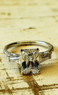 Who says good things don't come in threes? The emerald cut center stone on our white gold ring has two diamond stones that act as wings to give it nice lift.
