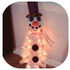 Marv the snowman! A $10 pre-lit tree from Walmart, two black ornaments for buttons, and all construction paper cutout for his face