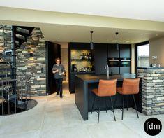 Moderne zwarte Fenix keuken met een granieten aanrechtblad en zwart inbouwapparatuur. De taatsdeur is prachtig verwerkt in deze keuken.