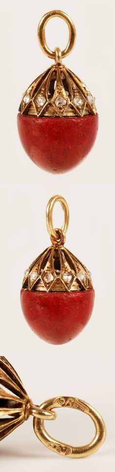 A Faberge gold, gem-set, and purpurine miniature pendant egg, workmaster August Holmstrom, ST Petersburg, circa 1900. The purpurine egg capped by an openwork gold cage set with mine-cut diamonds.