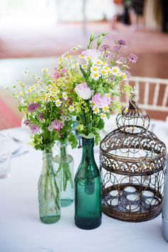 Daisies and wildflower table centre pieces with vintage bottles used as vases.  Rustic table plan idea for a quirky outdoor wedding, using a vintage suitcase, using stamped names on brown recycled paper.  From 'An Eco-Friendly Woodland Wedding With Sofas Swinging In The Trees!' on www.lovemydress.net.  Photography http://www.sarahleggephotography.co.uk/