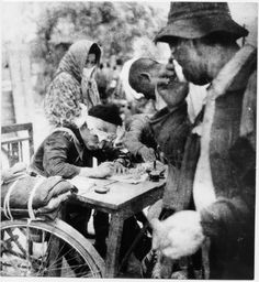 Soldier at table with victims of US atomic bombing of Hiroshima, 6 August, 1945. Photographer: Yoshito Matsushige. S)