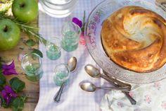 Still life de tarta de requesón con manzanas verdes, romero, flores purpuras, y cucharillas de plata antiguas