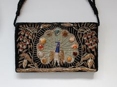 PEACOCK <3 Vintage black velvet clutch bag / with short handle,  featuring detailed peacock bird design. Featuring beads, metallic thread and 3d gemstones. Three strand short rope optional handle . Vintage Condition - some loose threads, non detracting from overall effect. Interior impeccible condition. Fastens with metal popper  Small Bag - Will fit smartphone ! Measures: (length) 8  (height) 5 x (depth approx) 2   For more Vintage Treasures head back to our shop home…