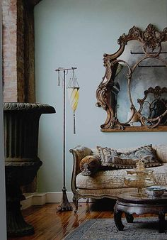 Duck egg blue walls, plush vintage velvet in subtle gold green blue shades, antique french furniture and a spectacular gilded mirror.
