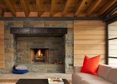 Guest house by Bohlin Cywinski Jackson nestled against a rugged stone wall at a coastal mountain range in California.