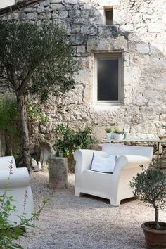 Olive trees, ancient brickwork wall,  gravel & ultra modern plastic furniture - awesome old new mix:
