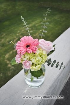 Pink and green flowers in a clear glass jar. (Garden rose, gerbera daisy, mini carnations, mini hydrangea, baby blue eucalyptus)