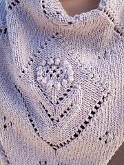 The center diamond is worked from the bottom up with a chart, then stitches are picked up to form the right and left sides of the shawl.