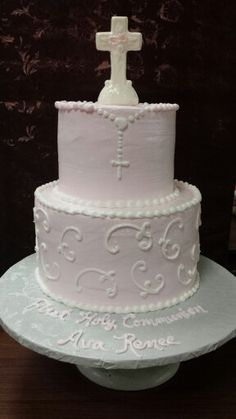 Tiered girls Communion cake in a blush pink. A piped rosary on the top tier with white chocolate cross topper.