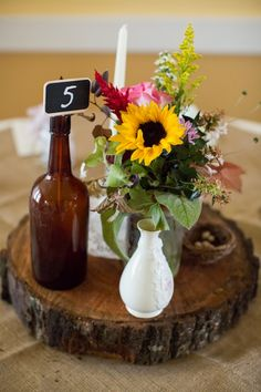 A Rustic wedding log centerpiece with beer bottle and sunflowers.