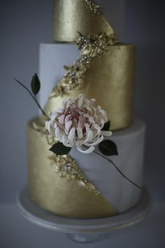 Wedding cake with sugar chrysanthemum and gold bas relief detailing, from Victoria Made.