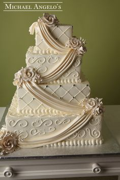 Classic Elegance #10Drapery  This four tier square ivory buttercream cake makes for a beautiful elegant occassion. Each layer is accented with fondant drapes that are lustered. The criss cross pattern and swirls are done with buttercream and then accented with gems. The corners also have gum paste roses to bring everything together.