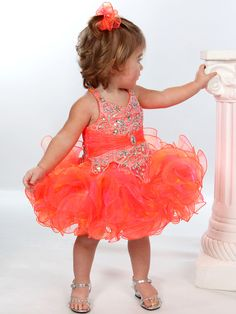 Your baby girl will be the center of attention when showcasing this gorgeous pageant creation from Unique Fashion UFB038 that features a halter v-bodice decorated with crystal-beaded patterns and a ruched band with center brooch around the empire waist. The mesmerizing organza skirt is decked out in ruffles that'll make her the winner of the event. Compliment this dazzling cupcake dress with designer shoes and our cute jewels.