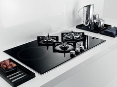 The Whirlpool AKT 477/IX black gas-on-glass hob features three burners alongside an induction zone. It offers cast iron supports and a 3.7kW wok burner.