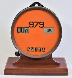 Antigo e raro relógio em metal para marcador de passageiros de transporte de bonde, com mostrador envidraçado. Base em madeira maciça. Registrava passageiros ida/volta, tabela e total. Alt.: 38cm. Comp.: 33cm.