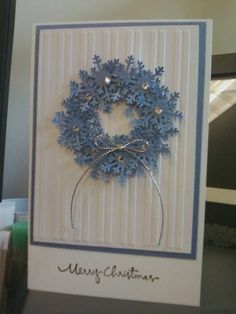 My new FAVORITE Christmas wreath card!  Because the snowflakes are blue and look fantastic.  The embossed white paper in the blue frame and silver embellishments make this a beautiful handmade card.