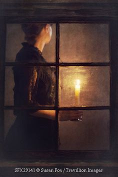 Trevillion Images - historical-woman-holding-candle-indoors