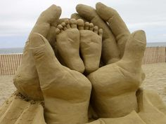 Escultura en arena, manos sosteniendo pies de bebe