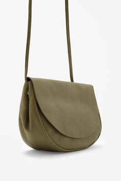 This rounded shoulder bag is made from soft grained leather with clean raw-cut edges and a cotton-lined compartment.. A functional design, it has a flap-over front, hidden magnetic fastening and a slim, adjustable strap.
