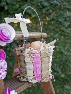 For a rustic-inspired basket, rip strips of Easter-themed fabric and weave it through a wire basket you can get at an antique shop. Fill with grass filler and brown hard-boiled eggs for a rustic look.