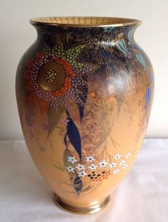 """An Art Deco Stunning Carlton Ware """"Babylon"""" pattern vase with loads of large Bell shaped and star shaped enamel flowers and leaves foliage,great shape on a rare light orange Matt ground colour,with multi colours,gold gilding trims and borders back stamped to base with Carlton Ware mark and pattern numbers. 
