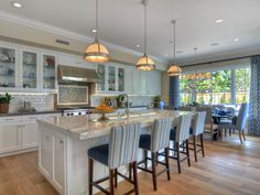 A beautiful aspect of this great room is the bright white kitchen. Some of the details include three chrome hanging lights above the spacious island which is covered in white and gray marble. The island counter extends to provide extra seating for guests to enjoy the company of the home chef.