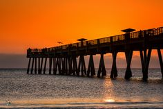 A silhouette of the Jacksonville Beach Pier as the sun begins to rise over the Atlantic Ocean in Florida.