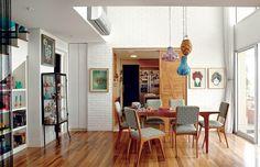 A sala de jantar tem mesa e cadeiras estilo anos 1950, garimpadas em feirinhas de antiguidades e forradas com tecido do Estúdio Zero, do Recife, e pendentes da Ethnix. Ao fundo, na parede de tijolos aparentes, a porta de correr que leva à cozinha (Foto: Victor Affaro)