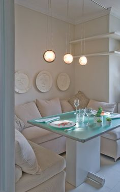 Dining booth/nook in off white but the glass table top adds that splash of colour. #booth #nook
