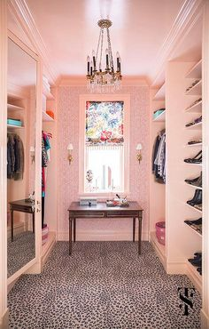 Pink walk-in closet features walls clad in pink geometric wallpaper lined with pale pink builts filled with clothes flanked by a wood console table finished with gold trim tucked under a window dressed in a colorful roman shades, A pink animal print rug leads to  stacked pink shoe shelves facing a pink framed mirror.