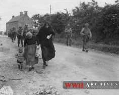 World War II Photograph: French civilians go on about their everyday tasks despite the fierce battles raging around them.  These women are overtaken on the road by passing Ranger units on their way to a new objective.