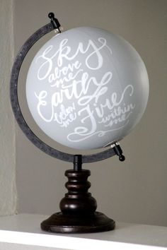 Scripted with Sky above me. Earth below me. Fire within me. this 14 inch tall, hand-painted globe is light grey with white hand-lettering, on a