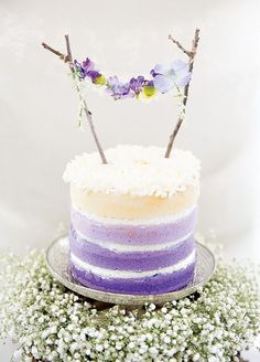Cake love: a dainty twig and flower bunting cake topper for a lavender-hued wedding cake