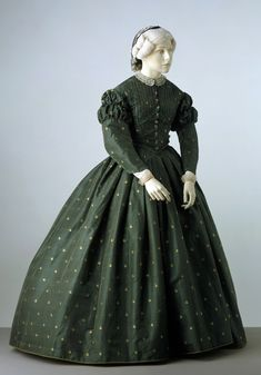 Green silk dress, English, ca. 1862. Dress with long puffed sleeves comprising bodice, skirt, and belt. Woven green silk with white floral design and trimmed with silk braid and beads, lined with glazed cotton, and edged with brushed braid. Victoria & Albert Museum